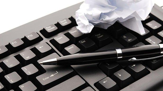 tangentbord med penna och hopknycklat papper
