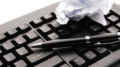 tangentbord och penna med papperslapp