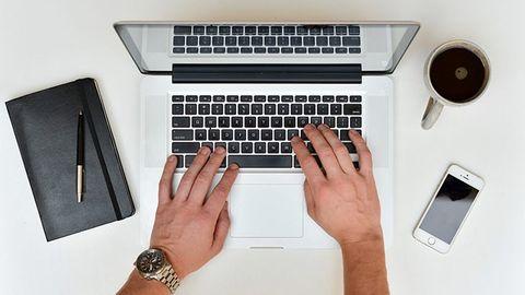 händer på tangentbord ovanifrån