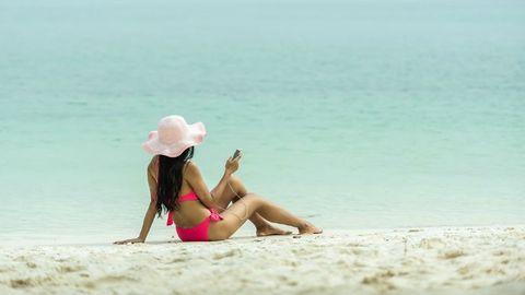 Tjej som använder telefonen på stranden