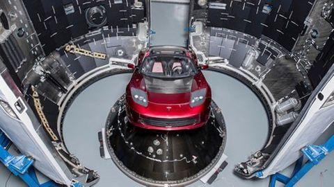 Röd Tesla på väg att lastas i en Falcon Heavy-raket