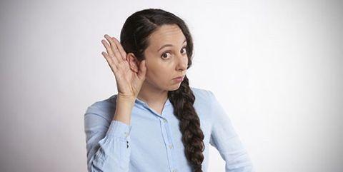Kvinna håller handen runt örat för att lyssna