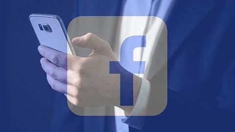 Facebook-logga med mobilanvändare i bakgrunden