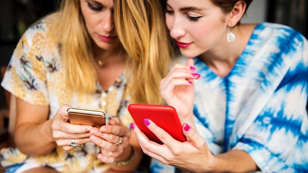Två kvinnor visar varandra mobilen